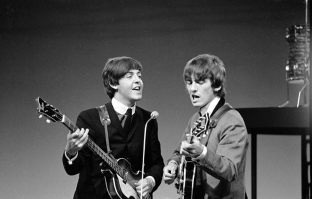 Пол Маккартни и Джордж Харрисон выступают в 1964 году.