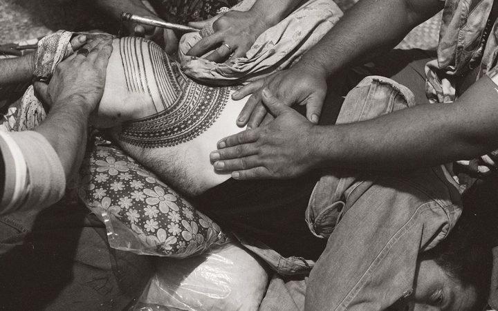 мужчине делают тату на Самоа